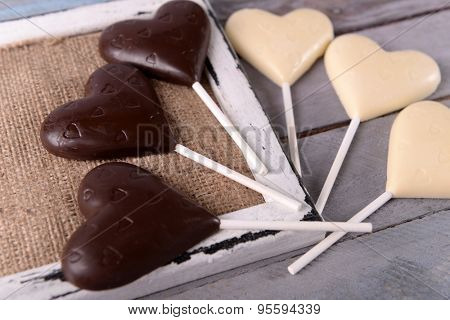 Chocolate heart shaped candies on sticks on wooden table, closeup