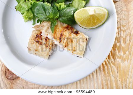 Dish of fish fillet with greens and lime on plate close up