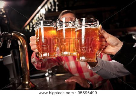 Happy friends clinking with beer mugs in pub,