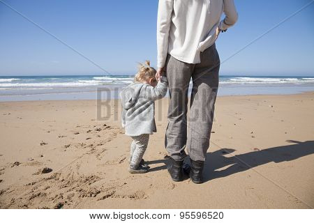 Baby And Mother Holding Hands Next To Ocean