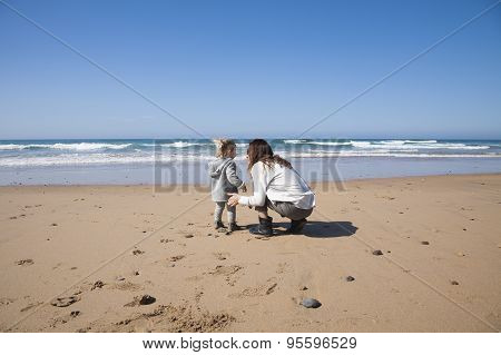 Baby And Mother Squatting In Beach