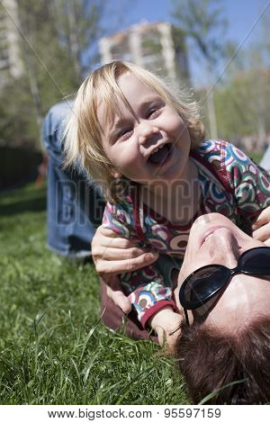 Happy Baby And Mom Lying On Grass