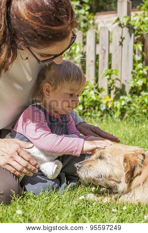Mother And Baby Petting Dog