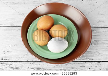 Group of eggs on plate on wooden background