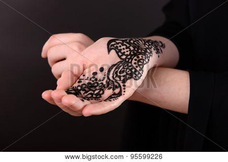 Closeup image of henna on female hand on dark background