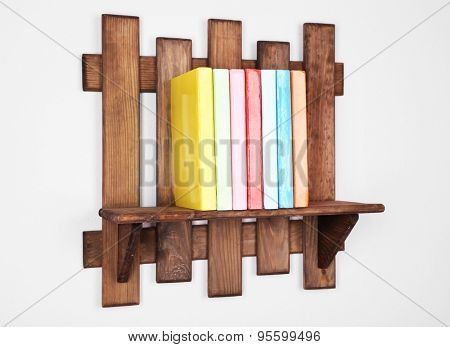 Wooden shelf with books on wall background