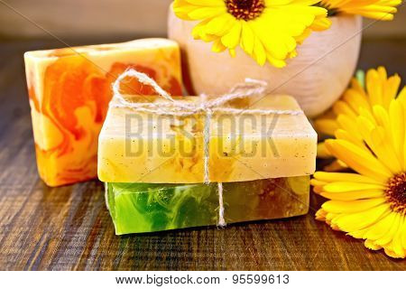 Soap homemade with calendula and mortar on board