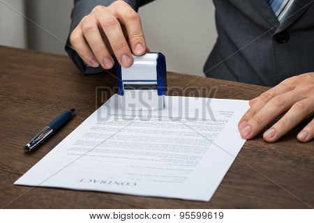 Businessman Stamping Document