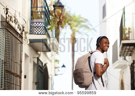 Smiling Young Man Traveling With Bag And Headphones