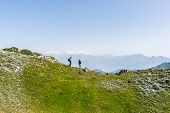 stock photo of italian alps  - Two people hiking uphill on footpath in the italian Alps - JPG