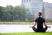 stock photo of pranayama  - Young woman sitting cross legged on river bank in front of modern office building meditating practicing yoga Easy Pose Sukhasana asana for meditation pranayama breathing back view copy space - JPG