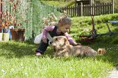 pic of baby dog  - blonde baby two years old age approaching crouching and touching a brown terrier breed dog lying on green grass lawn - JPG