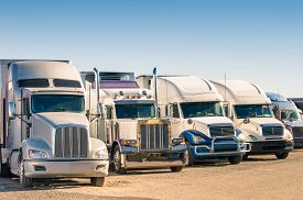 picture of truck-stop  - Generic semi truck in perspective row at a parking lot - JPG