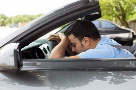 stock photo of deprivation  - Closeup portrait tired young handsome man with short attention span driving his car after long hours trip trying to stay awake at wheel isolated outside background - JPG