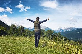 stock photo of plateau  - Man rejoicing with his arms outstretched as he stands on a plateau overlooking the Alps in the Berchtesgaden National Park - JPG