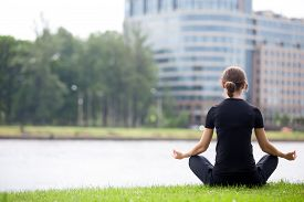 image of pranayama  - Young woman sitting cross legged on river bank in front of modern office building meditating practicing yoga Easy Pose Sukhasana asana for meditation pranayama breathing back view copy space - JPG