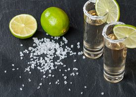 image of shot glasses  - Gold Tequila in Shot Glasses with Lime and Salt on black background - JPG