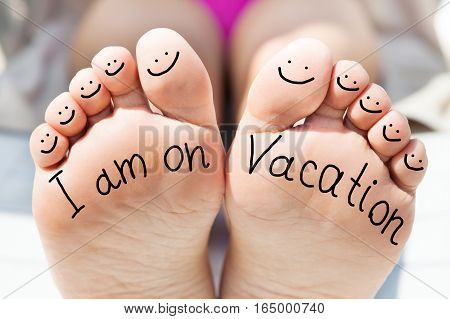 Close-up Of Person Feet With Handwritten Text And Smile Face On All Ten Toes
