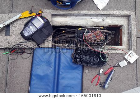 Phone cables and tools during the repair on the pavements