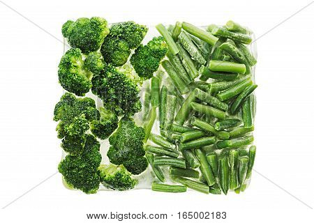 Briquette of fresh frozen green french bean and broccoli with hoarfrost closeup on white background. Isolated. Healthy vitamin food.