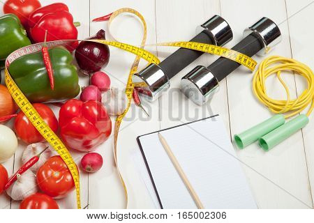 Sport and diet. Healthy lifestyle. Vegetables, dumbbells and notebook. Peppers, tomatoes, garlic, onions and radishes on a white background