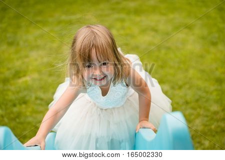 Little cute girl dressed in white playing on playground
