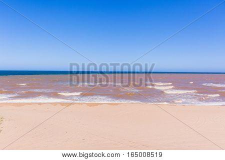 Brown river water flooding into blue ocean beach coastline