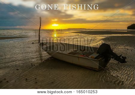 Word Gone Fishing on the background with fishing boat on the beach during sunrise.Fishing concept.
