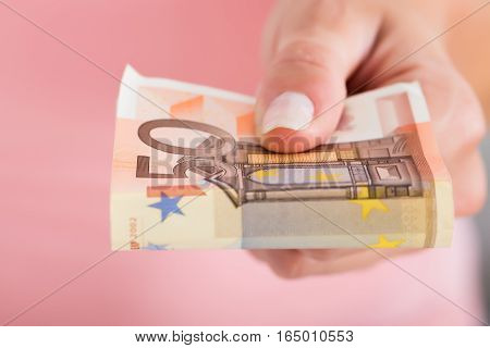 Close-up Of Person Hand Showing Folded Dollar Notes On Pink Background