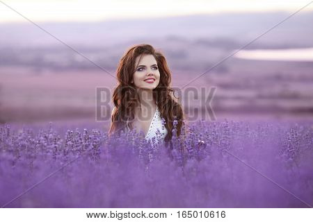 Beautiful Young Woman Portrait In Lavender Field. Attractive Brunette Girl With Long Curly Hair Styl