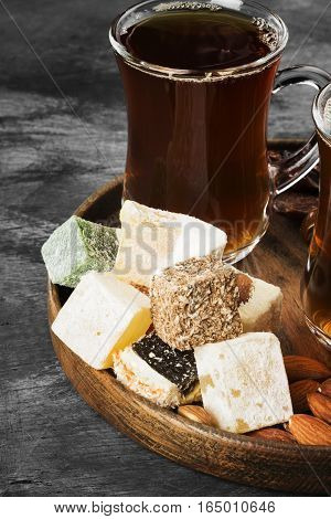 Black Tea, Oriental Sweets, Dates And Nuts On A Dark Background. Toning