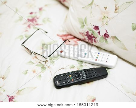 Remote controls and eye wear laid on the bed linen closeup with shallow depth of field