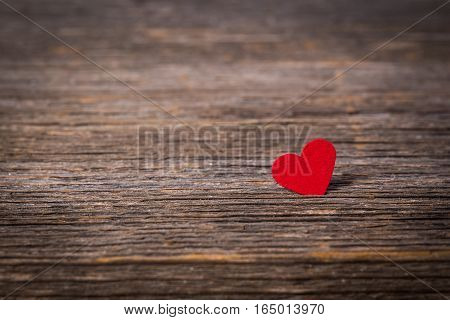 Red heart on old wooden background .