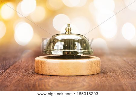 Close-up Of Service Bell On Wooden Desk