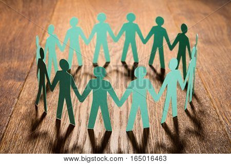 Cut Out Of Paper Representing People Holding Hands Together On Wooden Desk