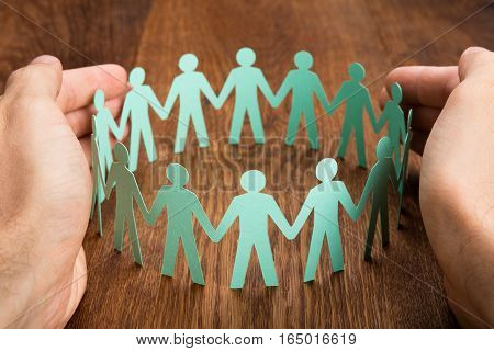 Close-up Of Person Hand Protecting Cut-out Figures On Wooden Desk