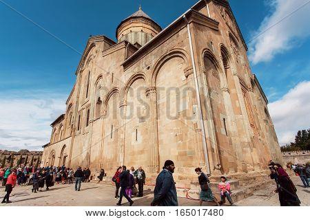 MTSKHETA, GEORGIA - OCT 14, 2016: Crowd of people walking around the famous orthodox Svetitskhoveli Cathedral, built in 4th century on October 14, 2016. UNESCO World Heritage Site.