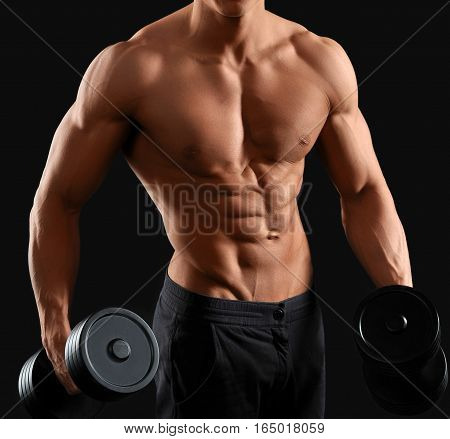 Body of God. Cropped shot of a strong and muscular male bodybuilder holding dumbbells against black background