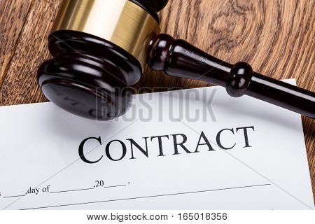 High Angle View Of Wooden Gavel On Contract Paper