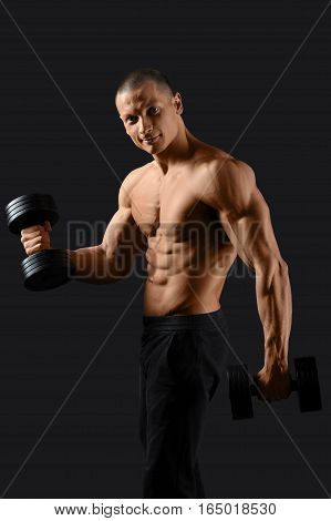 How workout is done. Happy male bodybuilder exercising with dumbbells smiling to the camera on black background
