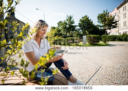 Woman watching video on smartphone sitting in park
