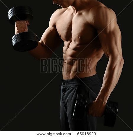 Muscles burning. Cropped shot of a shirtless bodybuilder working out with dumbbells showing off his toned torso