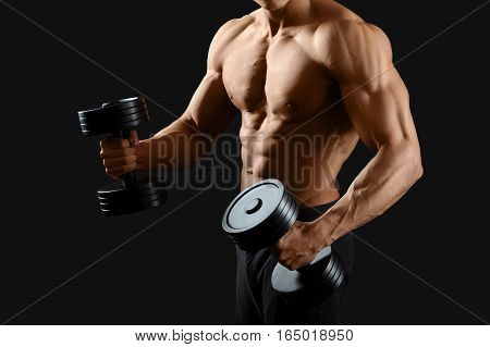 Powerful body. Cropped shot of a sexy hot male posing shirtless with dumbbells on black background