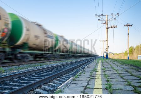 Train with oil tanks moving. Transportation of fuel on the railroad. Motion blur.