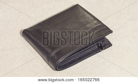 The leather black wallet on a light background