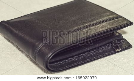 The leather black wallet on a light background close-up