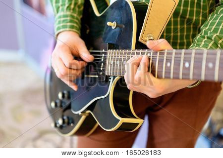 Man playing guitar on a stage. Musical concert. Close-up view.