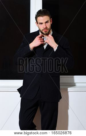 handsome young fashion bearded businessman with stylish hair in classic suit standing near window on white wall background