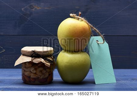 Fresh green apples turquoise tag string with different types of nuts in glass jar on blue vintage wooden background