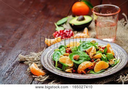 Spinach tangerines pomegranate avocado almonds walnuts salad.